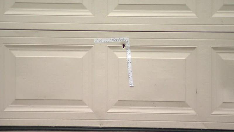 A hole from a bullet is seen in the garage door in Harris County, Texas. A 6-year-old boy is in...