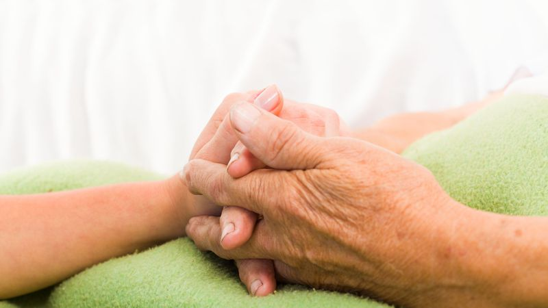 26421060 - health care nurse holding elderly lady's hand with caring attitude.