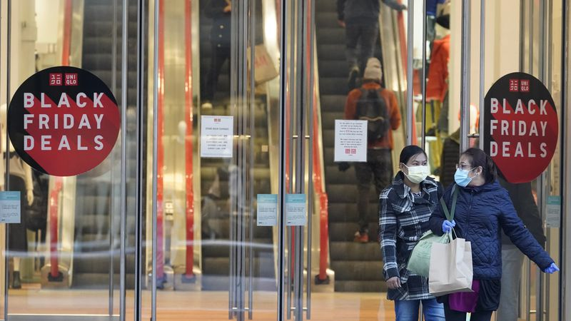Black Friday shoppers wear face masks and gloves as the leave the Uniqlo store along Fifth...