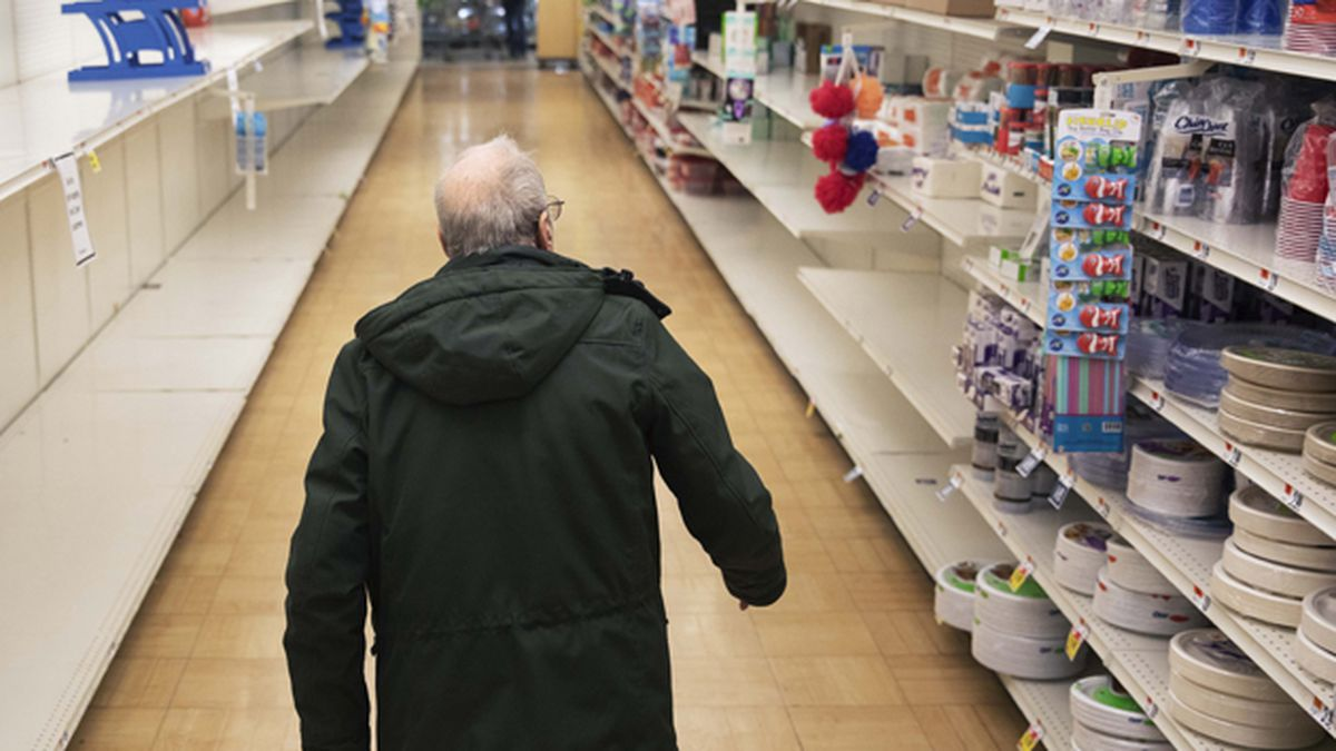 In this March 19, 2020 photo, a shopper looks for toilet paper at a Stop & Shop supermarket during hours open daily only for seniors in North Providence, R.I. Federal law enforcement is warning that scam artists are preying on older people's fears by peddling fake tests for the coronavirus to Medicare recipients. (AP Photo/David Goldman)