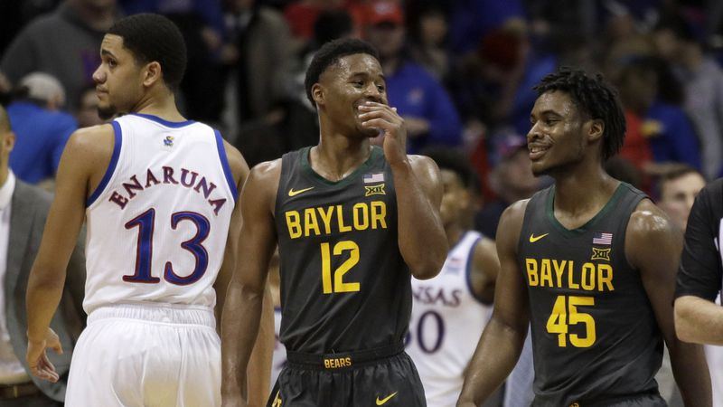 Baylor guard Jared Butler (12) smiles with teammate Davion Mitchell (45) while walking past...
