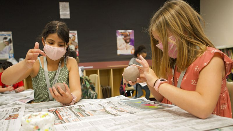 The fourth and fifth grade members of the school's Student Council are shaping ceramic soup...