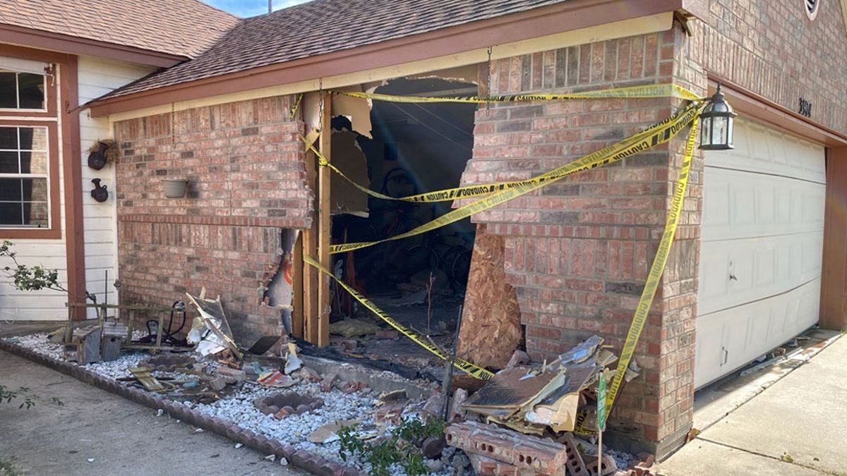 The crash left a gaping hole in the side of the home's garage. (Photo by Brandon Hamilton)