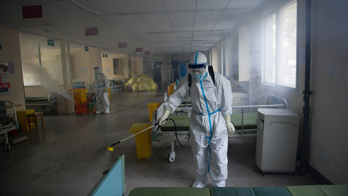 A worker disinfects around the No. 7 Hospital, once designated for only COVID-19 patients, in...