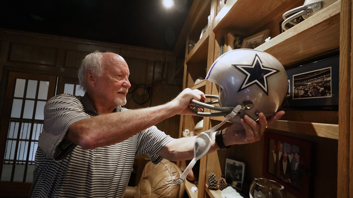 Former Dallas Cowboys and NFL football great Cliff Harris pulls out the helmet he wore during...