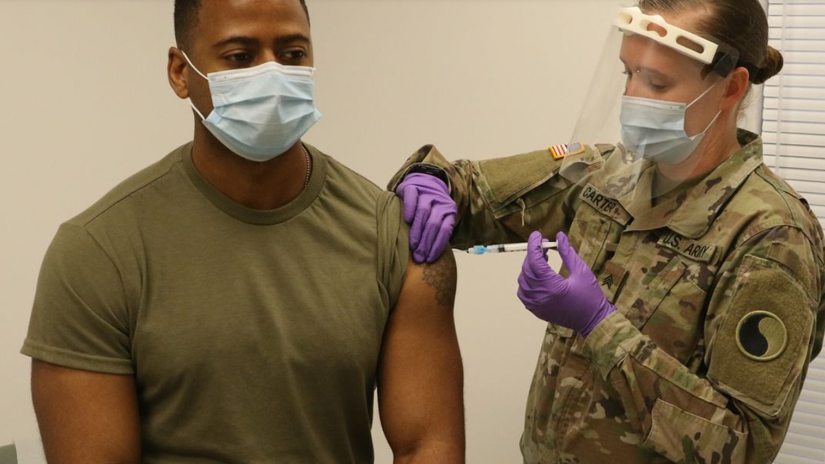 FILE:  Capt. Wilifred Hale receives a COVID-19 vaccination from Sgt. Anna Carter Dec. 31, 2020,...