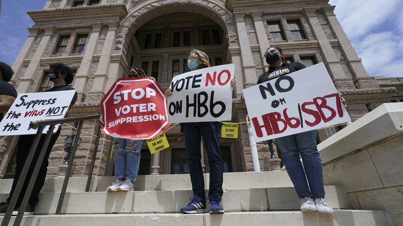 People opposed to proposed election bills House Bill 6 and Senate Bill 7 hold signs during an...