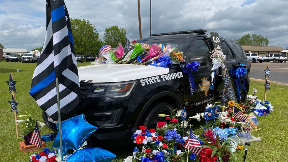 A DPS unit at Groesbeck Funeral Home is covered with flowers, cards and other items in memory...