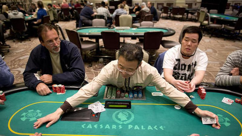 FILE - In this Feb. 27, 2013 file photo, dealer Han Kim, center, gathers up chips after a hand...