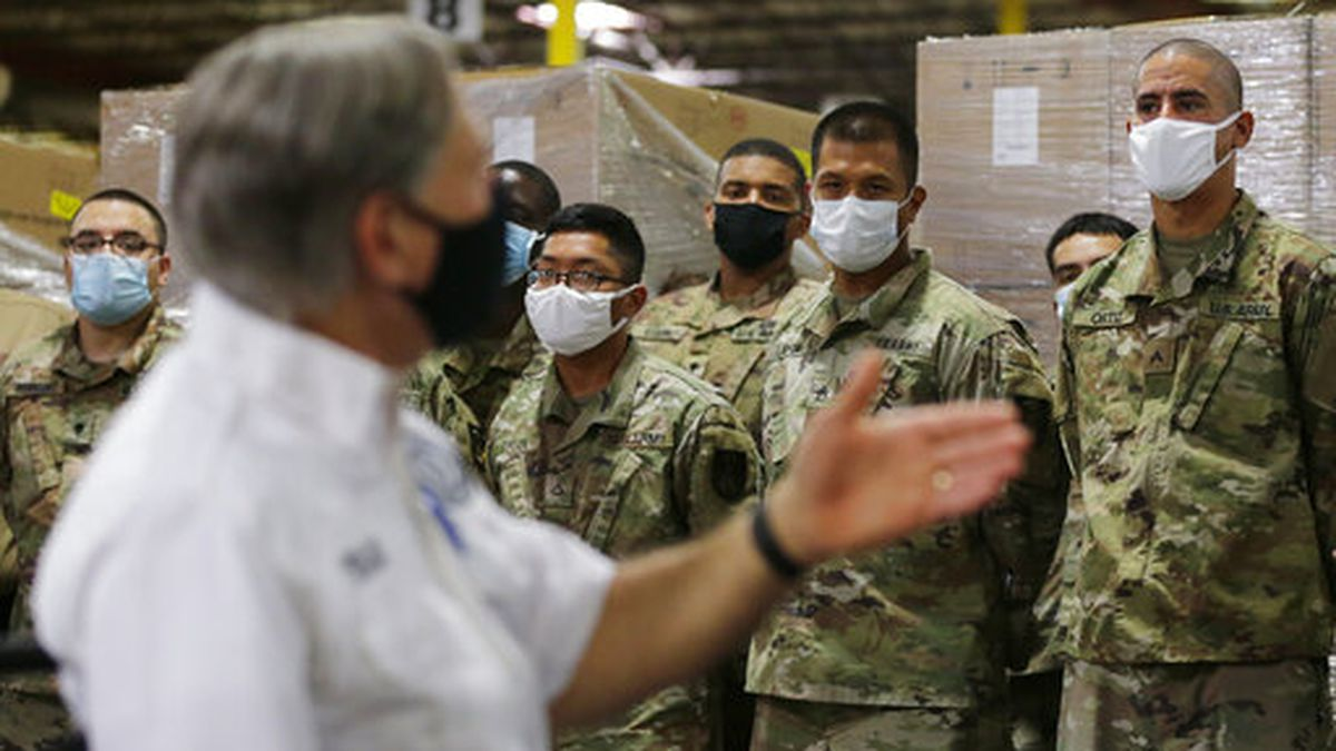 Texas Gov. Greg Abbott, foreground, addresses members of the National Guard during a visit to a...