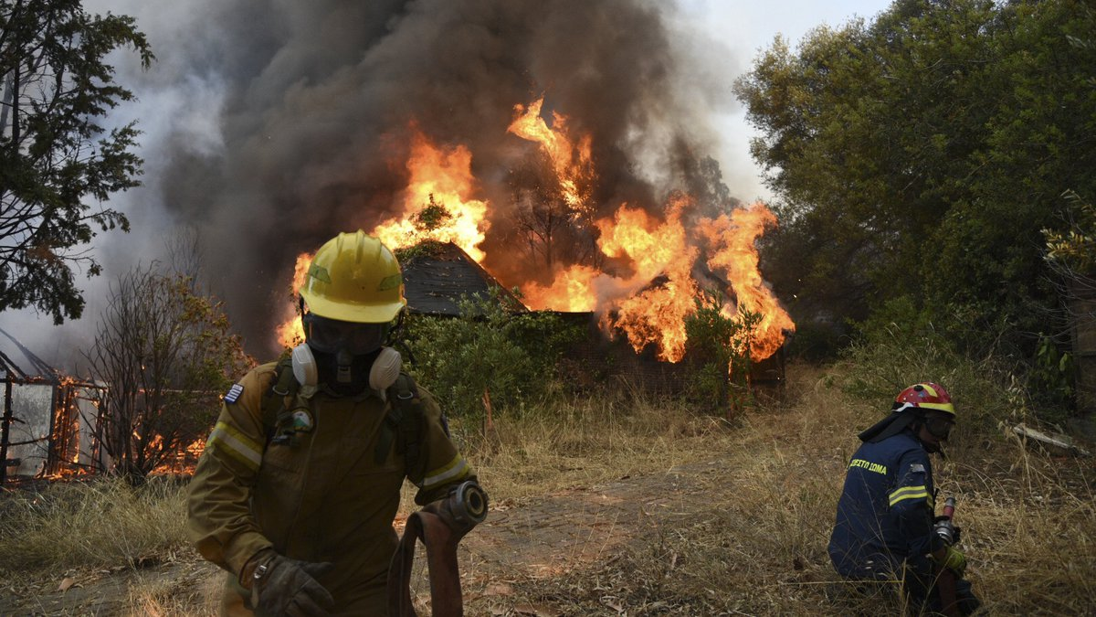 Firefighters operate during a wildfire near Lampiri village, west of Patras, Greece, Saturday,...