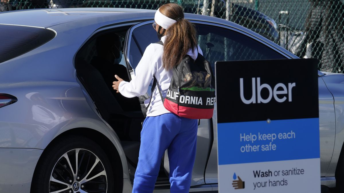 FILE - A traveler gets in the back of an Uber vehicle at Los Angeles International Airport in...