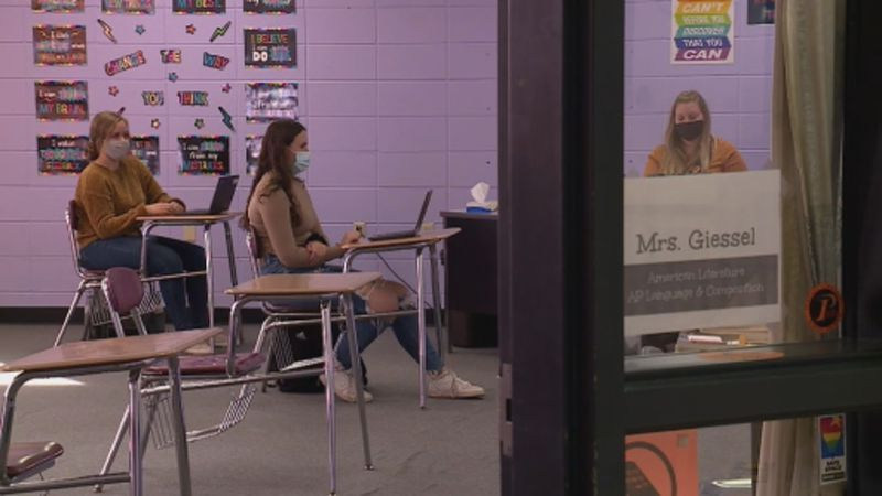 Nicole Giessel works with two students in her AP Language class.