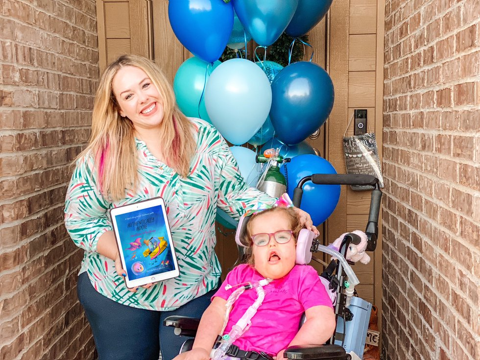 """Stephanie Wolfe and daughter Addie with w a copy of """"Authentically Addie: Adventures to the..."""