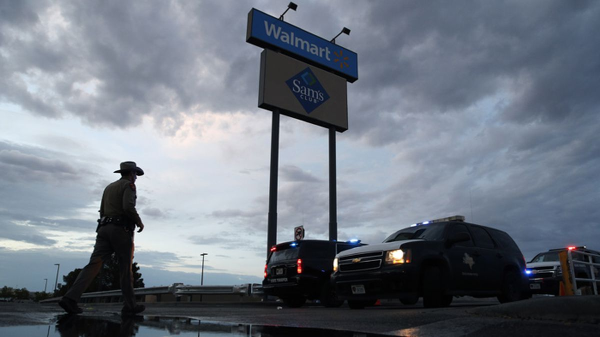 Law enforcement officials block a road at the scene of a mass shooting at a shopping complex...