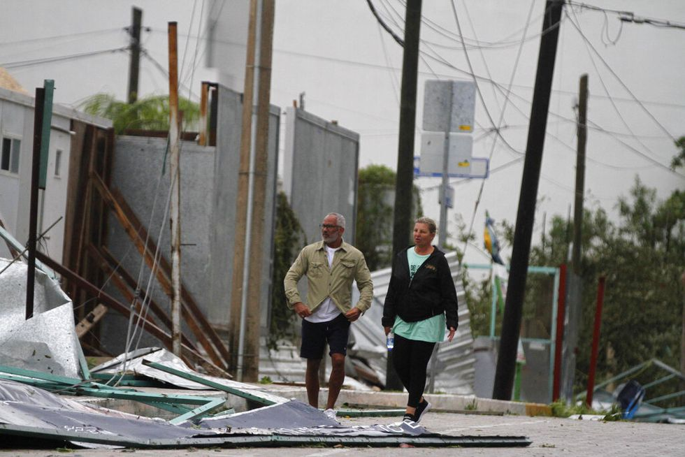 Tourists walk past debris littering the street after Hurricane Zeta's landfall in Playa del...