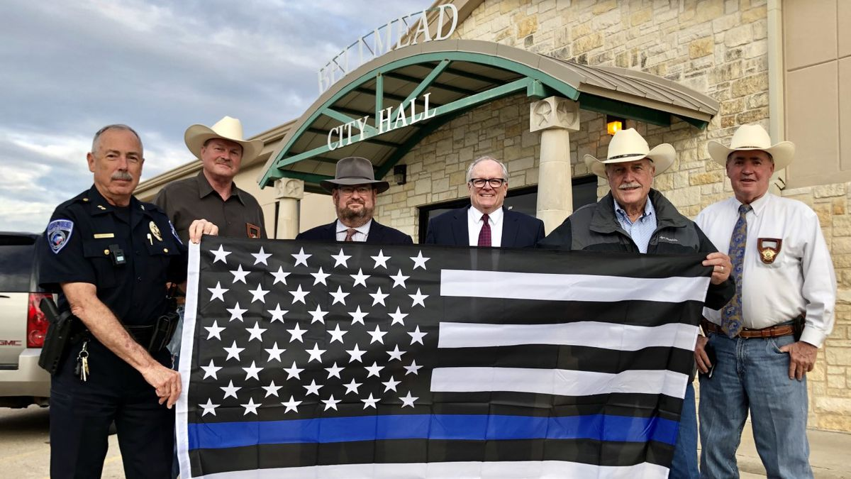 Bellmead's Chief of Police, Daniel Porter (far left) accepts a 'thin blue line flag' from his...