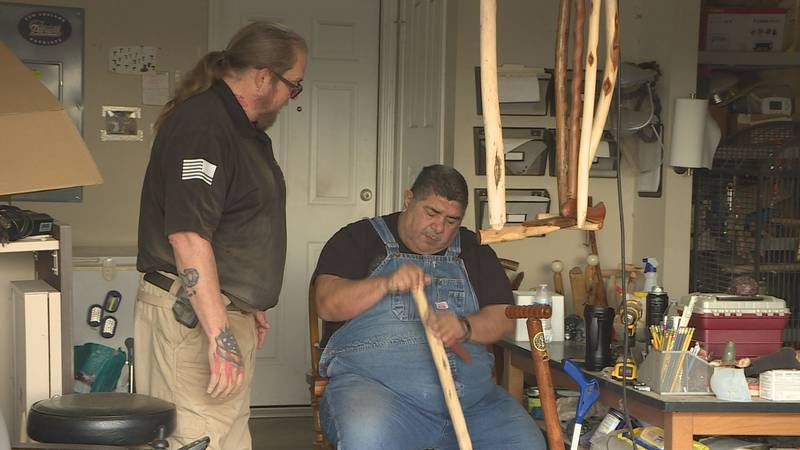 Jamie Willis (L) and David Garza (R) work on one of their hand-crafted canes.