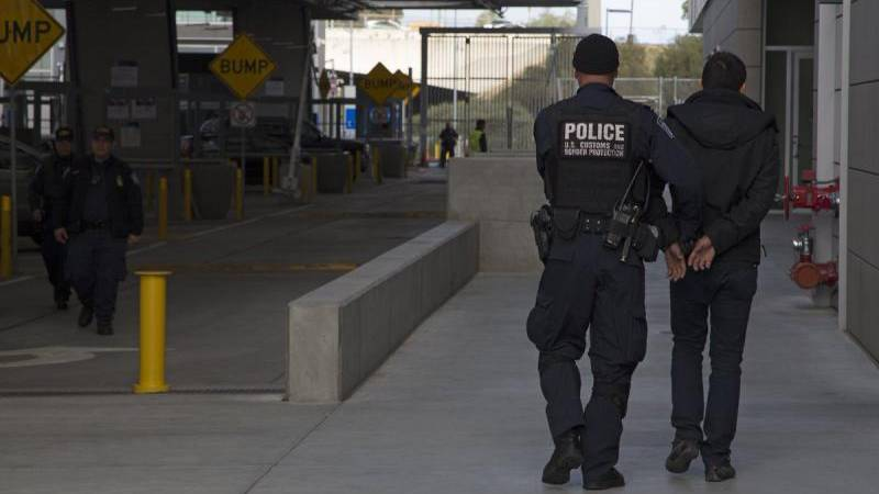 A CBP officer escorts a wanted person at a U.S. port of entry.