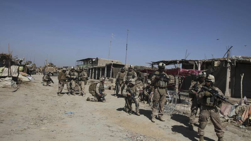 U.S. Marines with NATO forces patrol inwld a deserted market of Marjah, Afghanistan, Wednesday,...