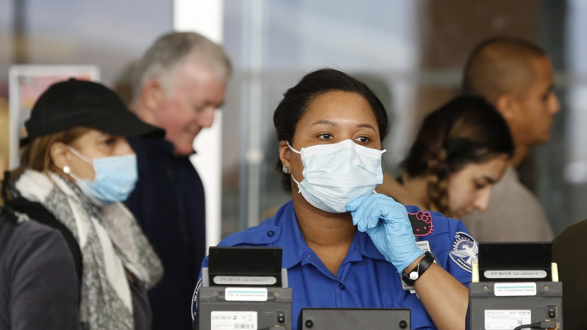 A Transportation Security Administration (TSA) employee adjusts her face mask while screening...