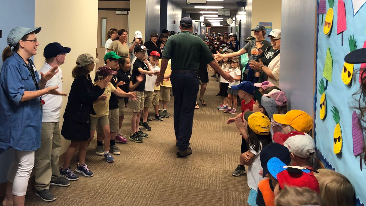 Students and staff members, all wearing caps, lined the hallway to salute the retiring janitor.  (Courtesy photo)