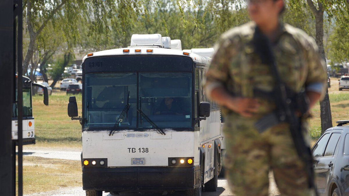 A National Guardsman stands at a gate along a border fence as a bus used to transport migrants,...