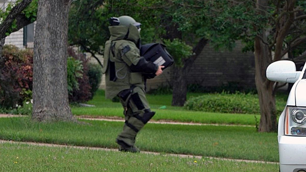A member of the McLennan County Sheriff's Office bomb squad carries the device found in the home.
