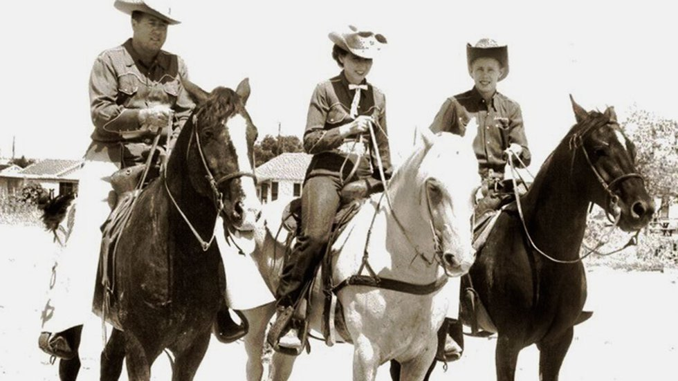 Bill Johnson (right) on horseback with his parents in an undated photo.