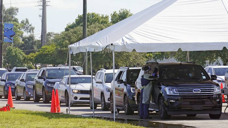 Cars line up at Miami Dade College North campus' COVID-19 testing site, Thursday, July 29,...