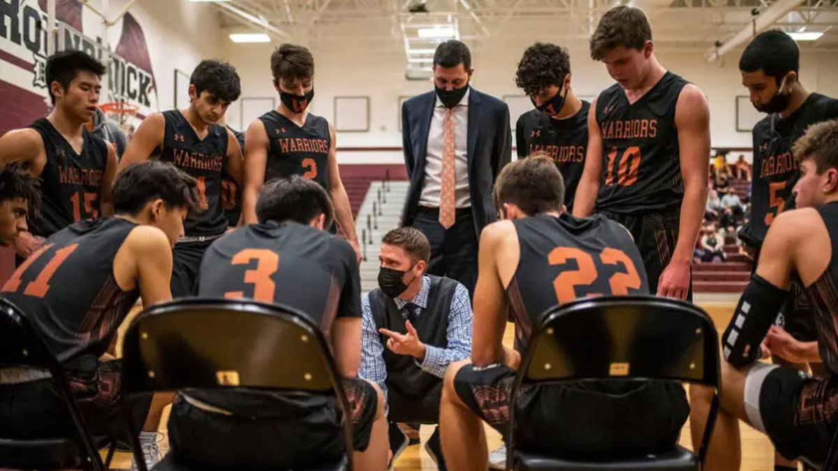 Westwood High School head basketball coach Brad Hastings speaks to his team during a time out...