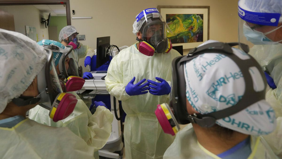 Medical personnel confer about COVID-19 patients.