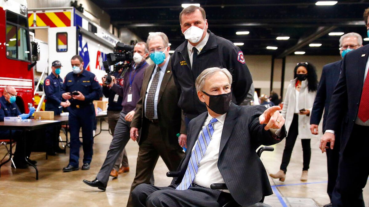 With guidance from Arlington Fire Chief Don Crowson, center, Texas Governor Greg Abbott...