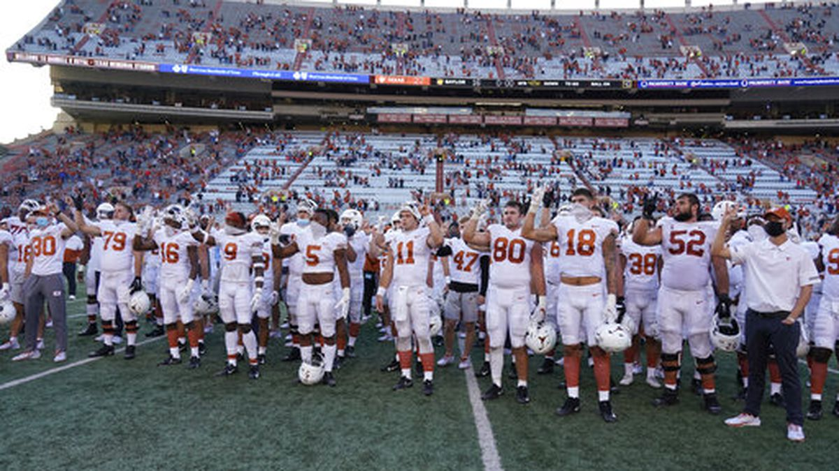 "Texas players, including Sam Ehlinger (11), sing ""The Eyes Of Texas"" after an NCAA college..."