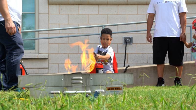 A young boy learns how to use a fire extinguisher at Fire Safety Day